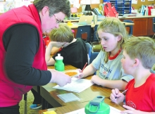 Kendra Crooks, an ISU Youth Outreach employee, helps Central students Caitlin Mussman and Blake Hunt plan a balanced meal and snack.